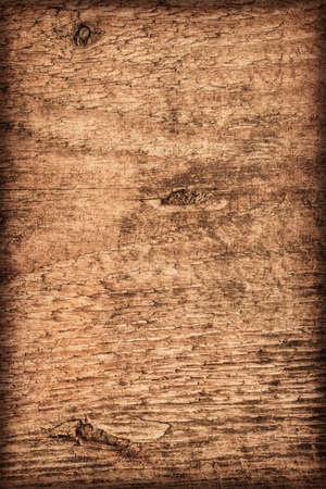 roughly: Photograph of old, roughly treated, weathered, cracked, knotted Pine plank, vignette grunge texture. Stock Photo