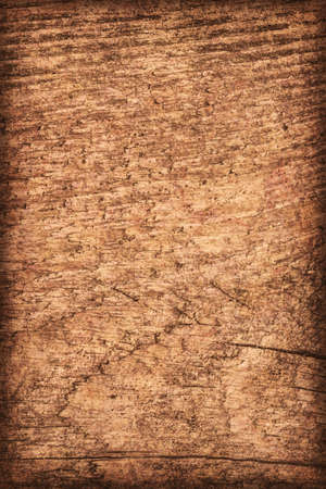 mottled: Photograph of old, roughly treated, weathered, cracked, knotted Pine plank, mottled, stained, vignette grunge texture.