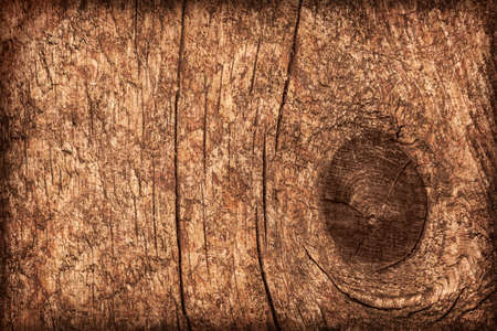 Photograph of old, roughly treated, weathered, cracked, knotted Pine plank, mottled, stained, vignette grunge texture.