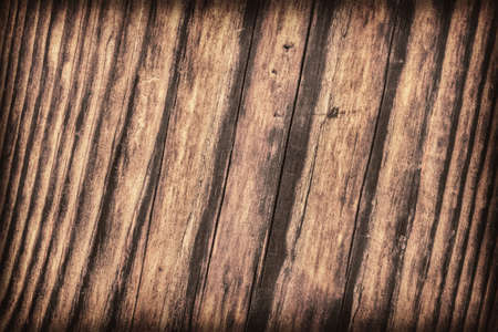 roughly: Old, roughly treated, weathered, cracked, rotten, knotted Pine plank, vignette grunge texture. Stock Photo