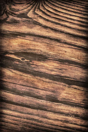 treated: Old, roughly treated, weathered, cracked, rotten, knotted Pine plank, vignette grunge texture. Stock Photo