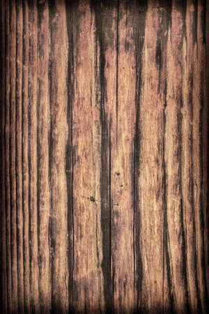 brunt: Old, roughly treated, weathered, cracked, rotten, knotted Pine plank, vignette grunge texture. Stock Photo