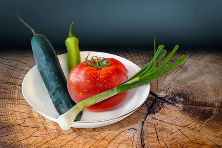 treated: Plate of Spring Vegetables, a fresh ripe Tomato, Cucumber, Spring Onion and Cayenne Pepper, placed on an old, wooden roughly treated, weathered, cracked Butcher Block.