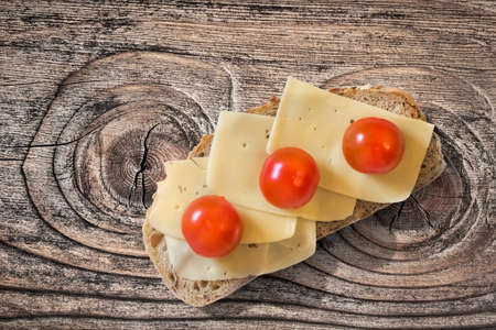 edam: Sandwich with three fresh ripe juicy Tomatoes and Edam Cheese slices, placed on an old, wooden roughly treated, weathered, cracked Butcher Block surface.