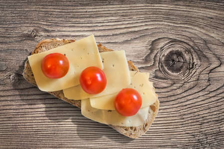 treated: Sandwich with three fresh ripe juicy Tomatoes and Edam Cheese slices, placed on an old, wooden roughly treated, weathered, cracked Butcher Block surface.