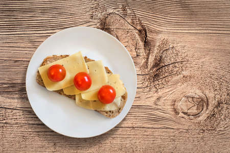 edam: White Porcelain Plate, with Sandwich made of three fresh ripe juicy Tomatoes and Edam Cheese Slices, placed on an old, wooden roughly treated, weathered, cracked Butcher Block surface.