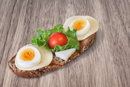 vegetable carbon: Light Sandwich, with Toasted slice of Whole Grain, Integral, Brown Bread, Edam Cheese and Hard boiled Egg Slices, Cow Cheese, Lettuce and Cherry Tomato, On Walnut table surface. Stock Photo