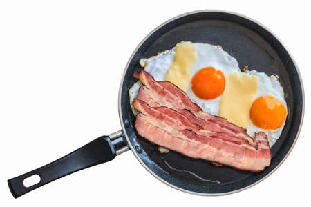 sunny side: Pair of Belly Bacon rashers with two Sunny Side Up Fried Eggs, in frying pan, Isolated on White Background.