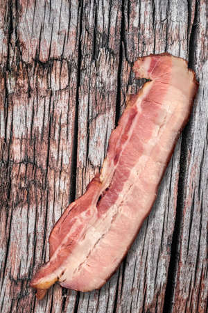 rasher: Pork Belly Rasher, placed on old, rough, knotted Wooden Surface.