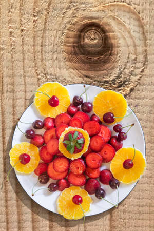 plateful: Plateful of Orange and Strawberries slices, with Cherries, placed on old, weathered, knotted, wooden table.