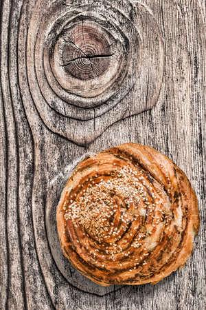 triglycerides: Croissant S�samo Hojaldre Roll, en la vieja, anudado, resistido, agrietado superficie de madera.