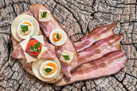 rasher: Toast Sandwich with Pork Bacon Rasher, and three extra Bacon Rashers, Ham, Edam and White Cow Cheese, hard boiled Egg slices, Cherry Tomato and Mayonnaise, on Old, Weathered, Cracked Wood surface. Stock Photo