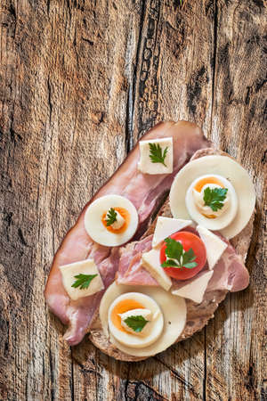 edam: Toast Sandwich with Pork Bacon Rasher, Ham, Edam and White Cow Cheese, hard boiled Egg slices, Cherry Tomato, Mayonnaise and Parsley leaves, on Old, Weathered, Cracked Wood surface.