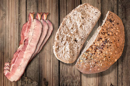 integral: Pork Belly Rashers, Integral Bread Loaf half and the cut Bread Slice, on Old Wooden Background.