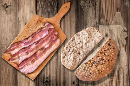 bread loaf: Tagliere con Rashers Pancetta, Integral met� Pagnotta e il pane tagliato Slice, sul vecchio fondo in legno.