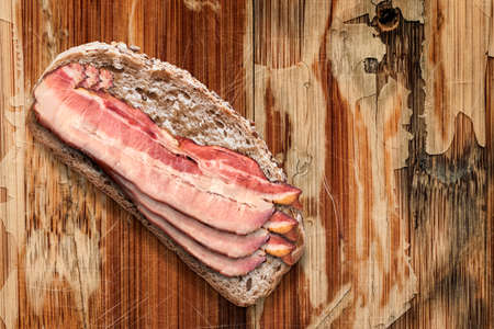 peeled off: Integral Bread Slice with Pork Belly Rashers, on weathered, scratched, old varnish peeled off Wooden Background. Stock Photo