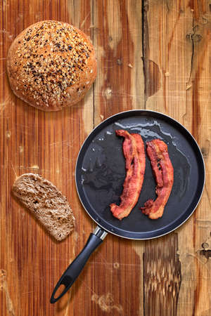 bread slice: Fried Belly Bacon Rashers in Teflon Frying Pan with Bread slice and Loaf alongside on old, cracked, scratched, peeled off, obsolete Wooden Table surface.