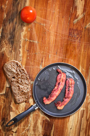 teflon: Fried Belly Bacon Rashers in Teflon Frying Pan with Bread Slice and Tomato alongside, on old, cracked, scratched, peeled off, obsolete Wooden Table surface.
