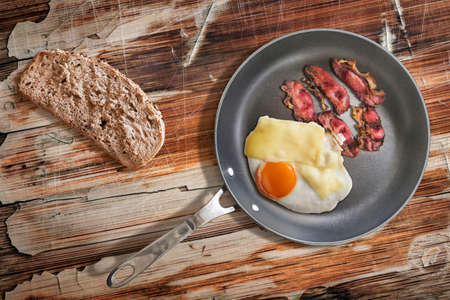 teflon: Fried Sunny Side Up Egg and Pork Ham Rashers in heavy duty Teflon Frying Pan with Integral Bread Slice alongside, on old, cracked, scratched, peeled off, obsolete Wooden Table surface.