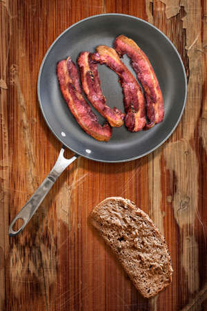 heavy duty: Fried Pork Belly Bacon Rashers in heavy duty Teflon Frying Pan with Integral Bread Slice alongside, on old, cracked, scratched, peeled off, obsolete Wooden Table surface.