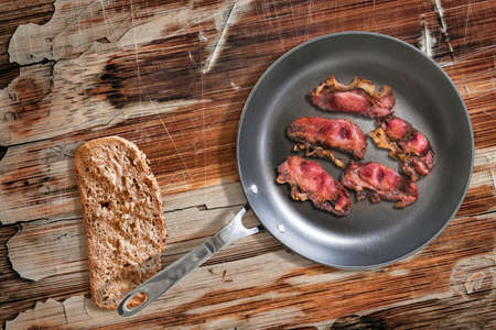 heavy duty: Fried Pork Ham Rashers in heavy duty Teflon Frying Pan with Integral Bread Slice alongside, on old, cracked, scratched, peeled off, obsolete Wooden Table surface. Stock Photo