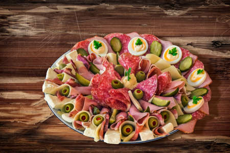 peeledoff: Plate of Serbian Meze, placed on very old, weathered, cracked, scratched, peeled off, Wooden Table. Stock Photo