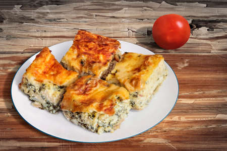 peeledoff: Plate of Freshly baked Serbian Traditional Zeljanica Spinach-cheese Pie slices, with Tomato, set on very old, weathered, cracked, scratched, peeled off, Wooden Table surface.