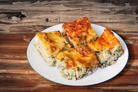 peeledoff: Plate of Freshly baked Serbian Traditional Zeljanica Spinach-cheese Pie slices, set on very old, weathered, cracked, scratched, peeled off, Wooden Table surface.