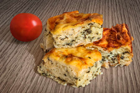 peeled off: Serbian Traditional Zeljanica Spinach-cheese Pie slices, with Tomato, set on very old, weathered, cracked, scratched, peeled off, Wooden Table surface.
