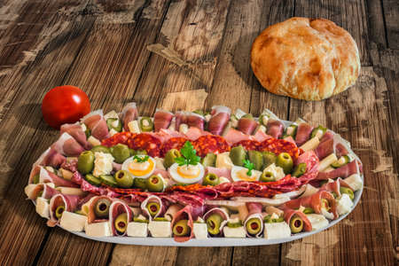 plateful: Plateful of Serbian Meze with domestic Pita Bread loaf and Tomato, placed on Wooden Table.