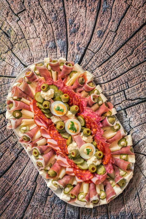savoury: Plateful of Savoury Appetizer Meze, placed on very old, weathered, cracked, rotten Log Cross Section Surface. Stock Photo