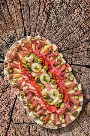 plateful: Plateful of Savoury Appetizer Meze, placed on very old, weathered, cracked, rotten Log Cross Section Surface. Stock Photo