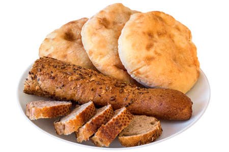 Porcelain Plate with three Pita Bread loafs and Baguette Integral Brown Bread cut in slices,  Isolated on White Background.