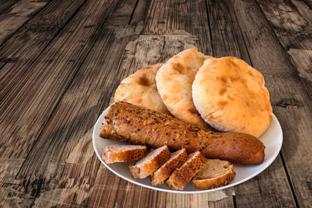 Porcelain Plate with three Pita Bread loafs and Baguette Integral Brown Bread cut in slices, on old Wooden Table.