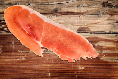 peeled off: Prosciutto Slices on very old, varnished, cracked, peeled off, scratched Wooden Table Surface.