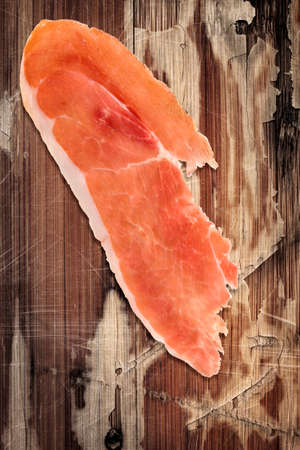 peeledoff: Prosciutto Slices on very old, varnished, cracked, peeled off, scratched Wooden Table Surface.