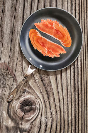 teflon: Prosciutto Pork Ham Rashers, in heavy duty Teflon Frying Pan, on Old, Cracked, Knotted Wooden Table surface.