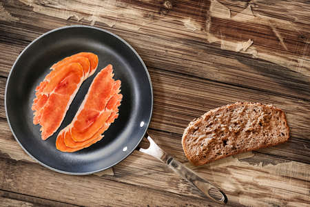 peeledoff: Prosciutto Pork Ham Rashers, in heavy duty Teflon Frying Pan, with Integral Bread Slice alongside, on very Old, Cracked, Scratched, Peeled-off Wooden Table surface. Stock Photo