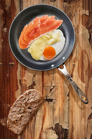 peeledoff: Fried Sunny Side Up Egg, with Edam Cheese and Prosciutto Pork Ham Rashers, in heavy duty Teflon Frying Pan with Integral Bread Slice alongside, on Old, Cracked, Scratched, Peeled-off Wooden Table.