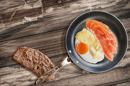 edam: Fried Sunny Side Up Egg, with Edam Cheese and Prosciutto Pork Ham Rashers, in heavy duty Teflon Frying Pan with Integral Bread Slice alongside, on Old, Cracked, Scratched, Peeled-off Wooden Table.