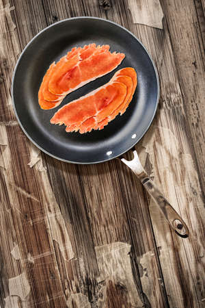 peeledoff: Prosciutto Pork Ham Rashers, in heavy duty Teflon Frying Pan, on very Old, Cracked, Scratched, Peeled-off Wooden Table surface.