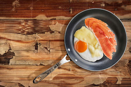 teflon: Fried Sunny Side Up Egg with Edam Cheese and Prosciutto Pork Ham Rashers, in heavy duty Teflon Frying Pan, on very Old, Cracked, Scratched, Peeled-off Wooden Table surface.