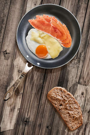 teflon: Fried Sunny Side Up Egg and Prosciutto Pork Ham Rashers, in heavy duty Teflon Frying Pan with Integral Bread Slice alongside, on very Old, Cracked, Scratched, Peeled-off Wooden Table surface