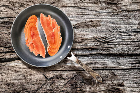 fryingpan: Prosciutto Pork Ham Rashers, in heavy duty Teflon Frying Pan, on very Old, Cracked, Wooden Table surface.