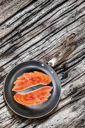 teflon: Prosciutto Pork Ham Rashers, in heavy duty Teflon Frying Pan, on very Old, Cracked, Wooden Table surface.