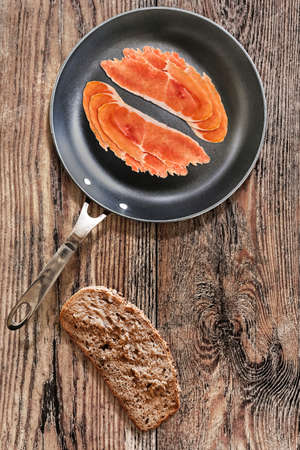teflon: Prosciutto Pork Ham Rashers, in heavy duty Teflon Frying Pan, with Integral Bread Slice alongside, on very Old, Cracked, Wooden Table surface.