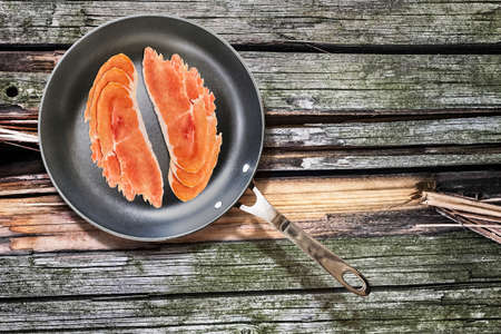 teflon: Cured Pork Ham Slices, in Teflon Frying Pan, on Old, Weathered, Cracked, Wooden Picnic Table covered with Moss Patches Stock Photo