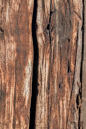 logging railway: Bituminous surface texture of an old weathered, rotten, cracked Square Timber Bollard, made of obsolete, scrapped Railroad Cross Tie Timber Stock Photo