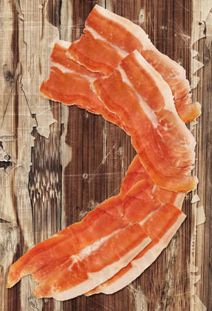 peeledoff: Dry Cured Smoked Pork Ham Prosciutto Slices Isolated on very Old Weathered Cracked Wooden Table Surface.