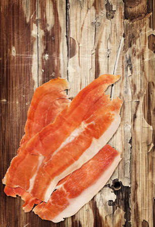 peeledoff: Dry Cured Smoked Pork Ham Prosciutto Slices on very Old Weathered Cracked Wooden Table Surface.